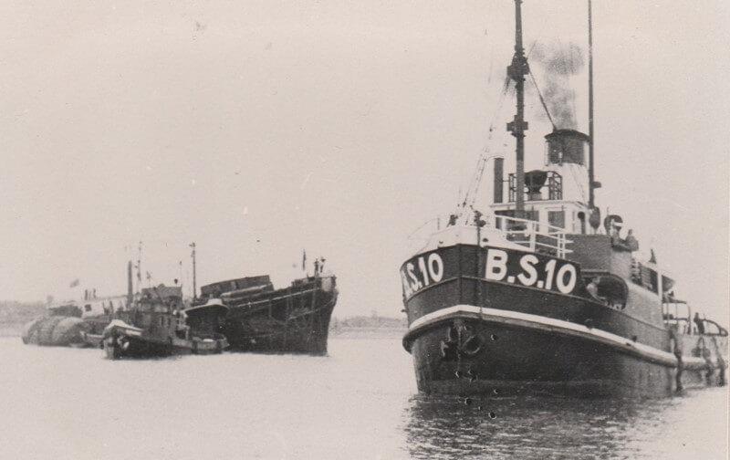 De sleper B.S.10 sleept het wrak de haven uit