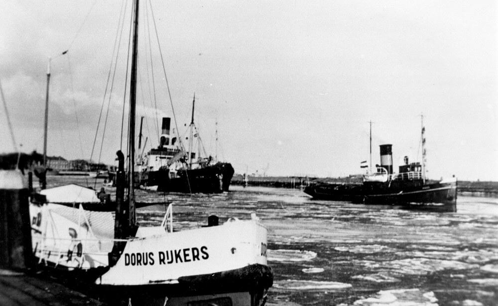 Aan de tros van de sleper Maas wordt de Lilian de haven van Den Helder binnengebracht